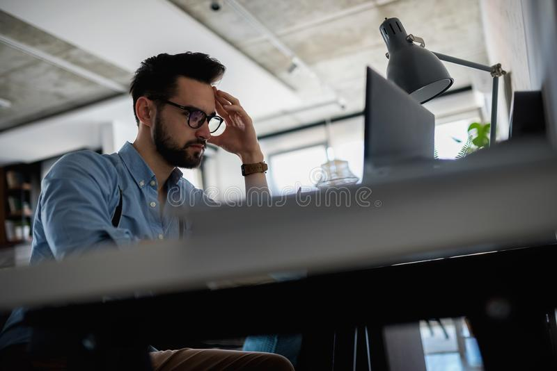 Young bearded businessman is sitting in front of computer, working. Freelancer, entrepreneur works at home. Young modern bearded man working with laptop stock photos