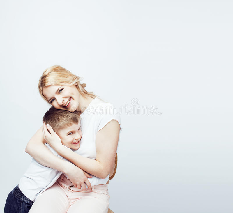 Young modern blond curly mother with cute son together happy smiling family posing cheerful on white background. Lifestyle people concept, sister and brother stock photography
