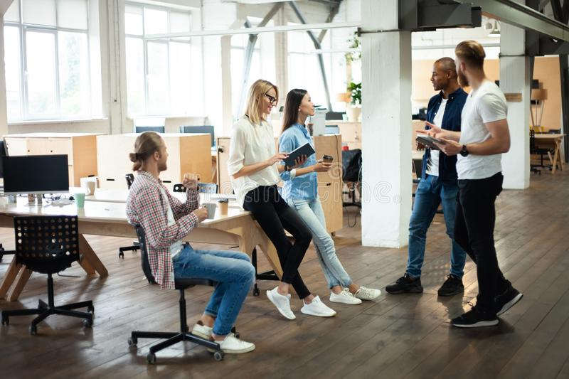Young modern colleagues in smart casual wear working together while spending time in the creative office. stock photos