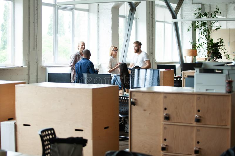 Young modern colleagues in smart casual wear working together while spending time in the creative office. royalty free stock images
