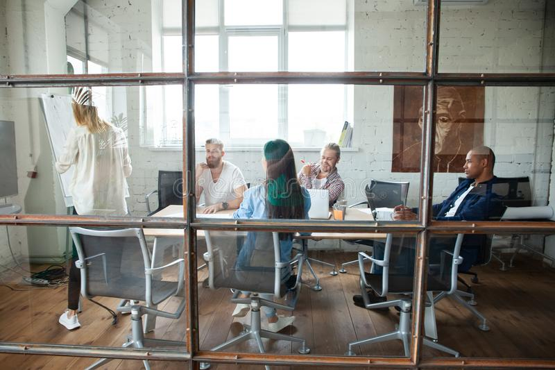Young modern colleagues in smart casual wear working together while spending time in the creative office. stock photography