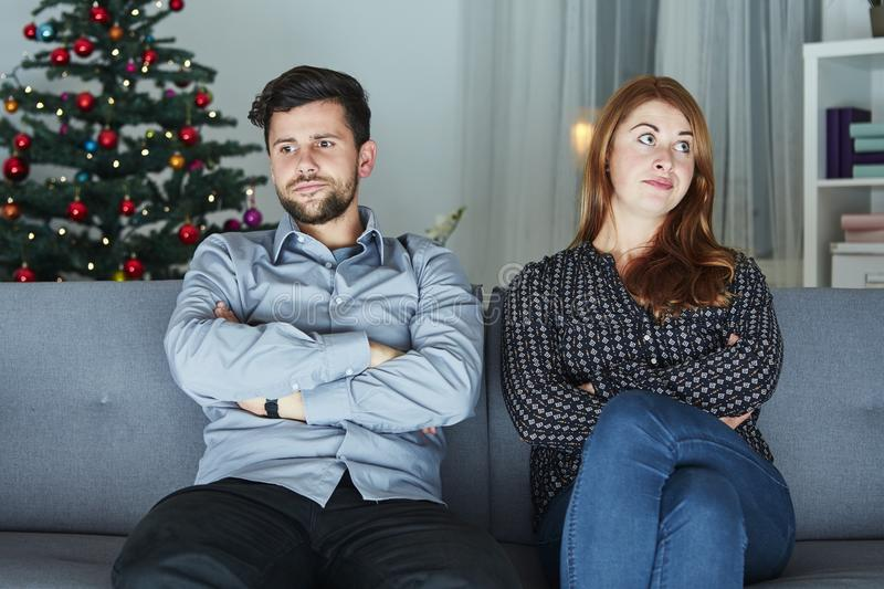 Young modern couple is irritated of christmas. With christmas tree in background stock photography