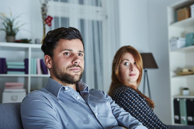 Young modern couple is irritated of christmas. With christmas tree in background royalty free stock images