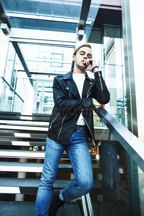 Young modern hipster guy at new building university blond fashio. N handsome boy, lifestyle people concept stock photo