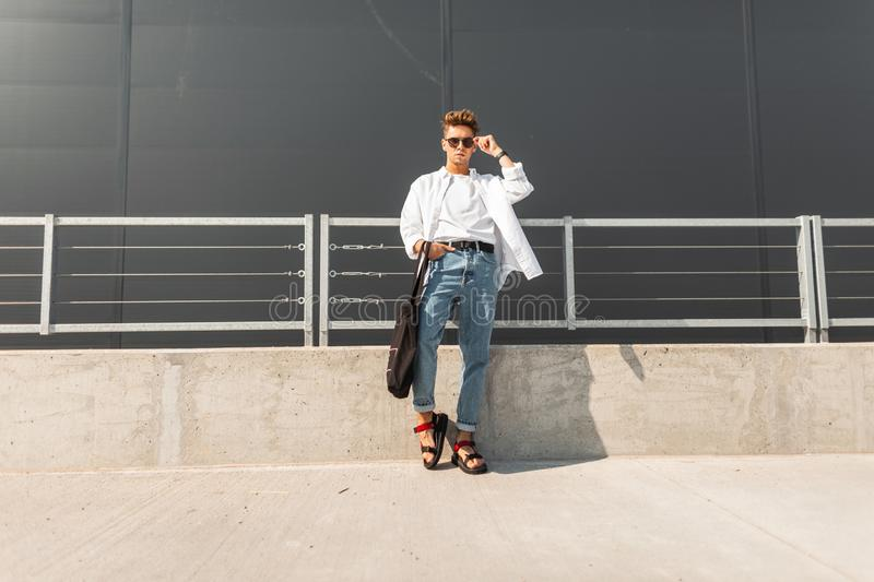 Young modern hipster man in a white shirt in blue jeans in sunglasses with a black bag in red sandals is standing in the city. On a sunny day. Handsome guy stock photo
