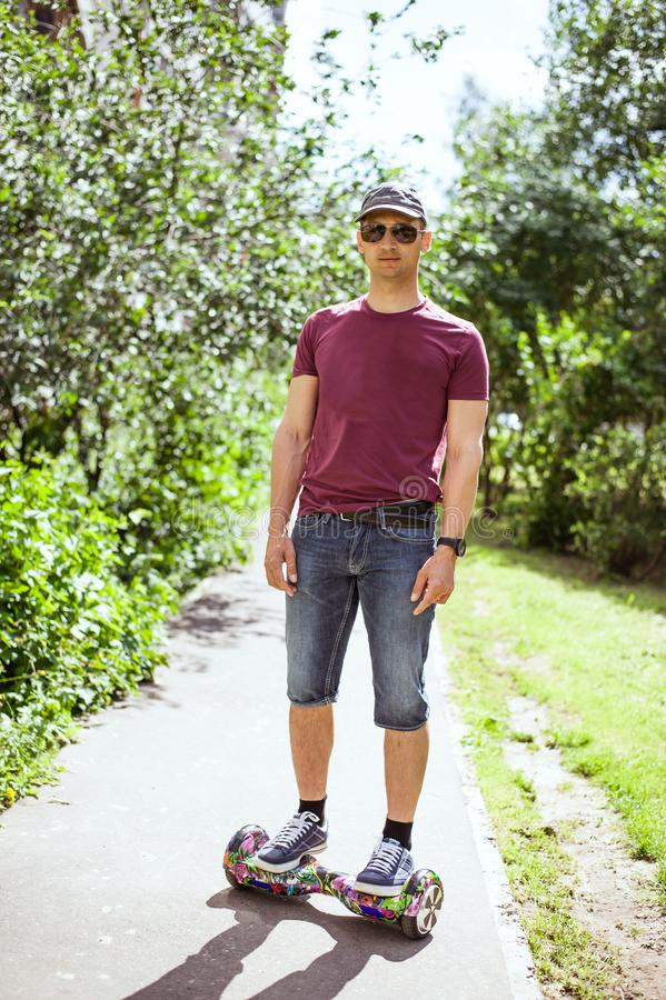 Young modern man in denim shorts and burgundy t-shirt rides around the city on hoverboard royalty free stock images