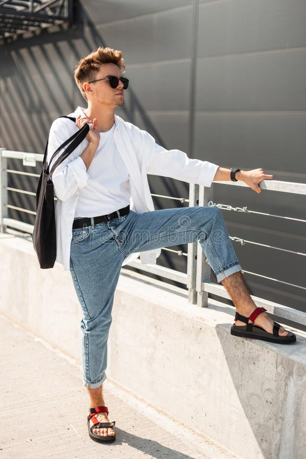 Young modern man model in trendy summer clothes in red vintage sandals in sunglasses with black bag relaxes near a gray building. On a sunny day. Handsome guy royalty free stock photos