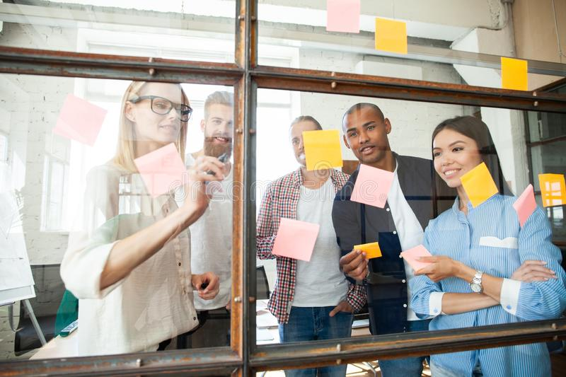 Young modern people in smart casual wear using adhesive notes while standing behind the glass wall in the board room royalty free stock image