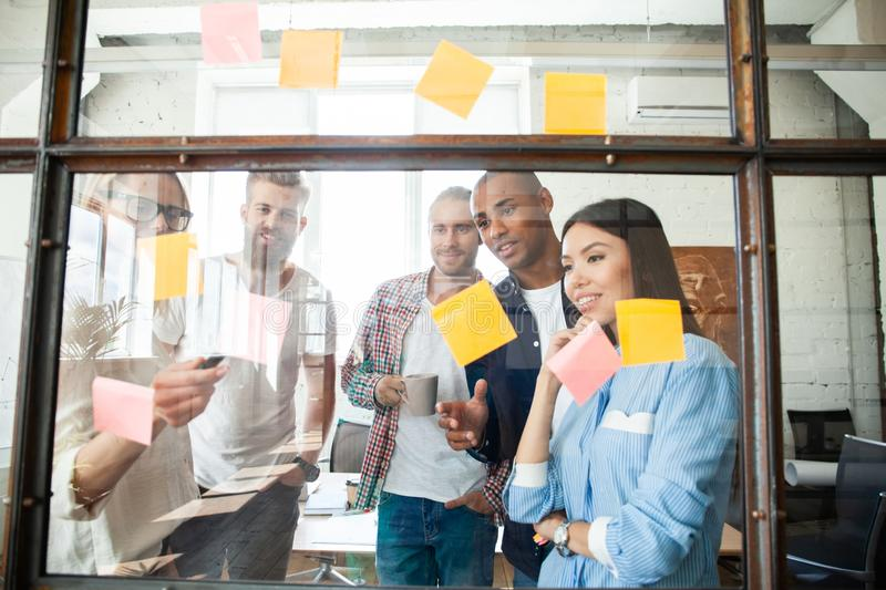 Young modern people in smart casual wear using adhesive notes while standing behind the glass wall in the board room royalty free stock photos