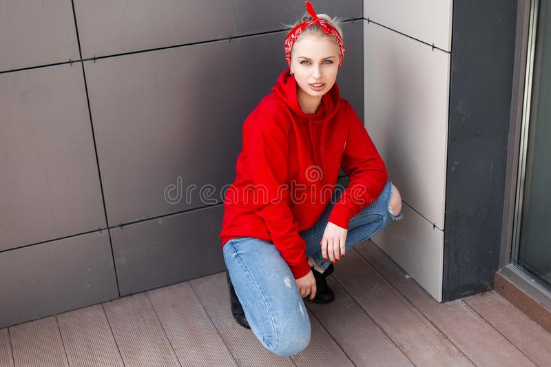 Young modern stylish woman in black boots in a red sweatshirt in ripped jeans with a fashionable bandana sitting outdoors. Near a gray wall. Beautiful girl stock images