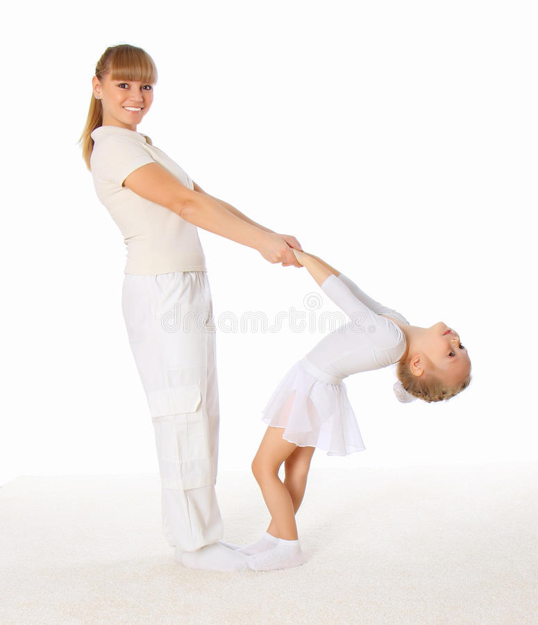 The young mom and her little daughter doing exerci royalty free stock images