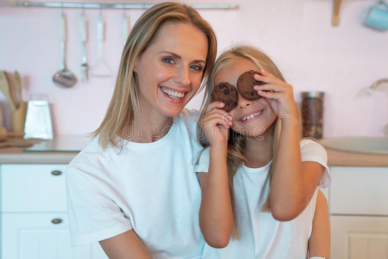 Young mom and her little daughter having fun holding chocolate chip cookies and smiling. Loving family stock photography