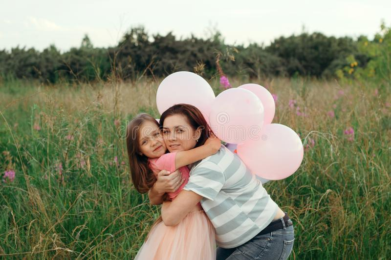 young mom kisses her little daughter on the cheek against the green background on a sunny summer day stock photography
