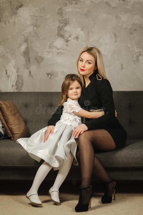 Young mom and little daughter at home sitting on sofa. Attractive mother in black dress. Happy family royalty free stock photography
