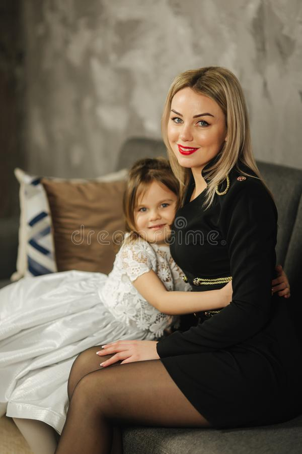 Young mom and little daughter at home sitting on sofa. Attractive mother in black dress. Happy family royalty free stock photos