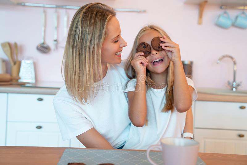 Young mom is looking at her little daughter having fun holding chocolate chip cookies and smiling. Loving family royalty free stock image