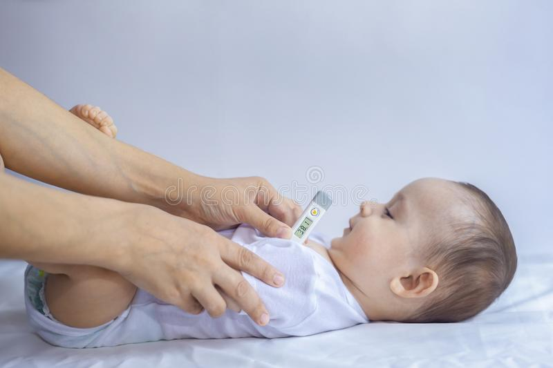Young mom measuring temperature of small sick boy. Using thermometer royalty free stock photos