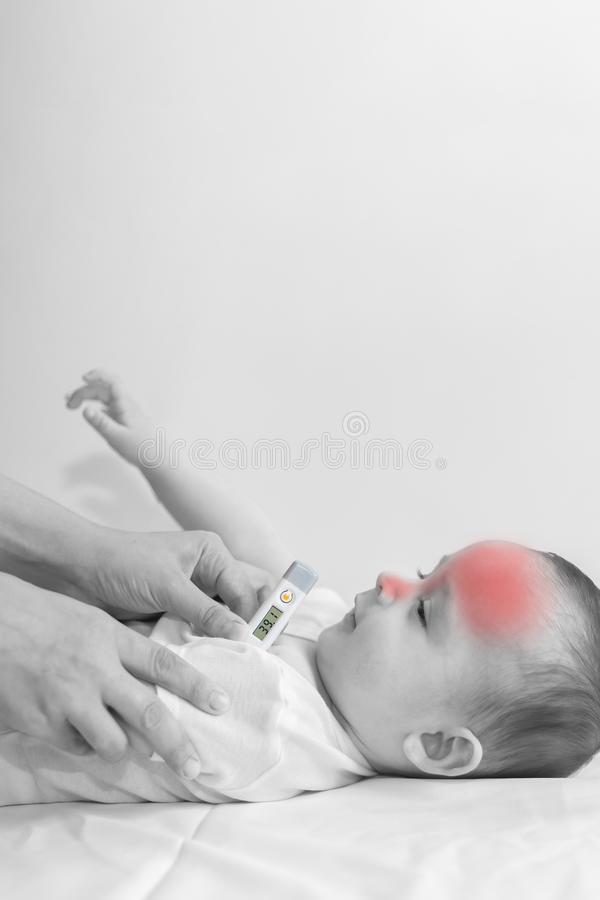 Young mom measuring temperature of small sick boy royalty free stock images