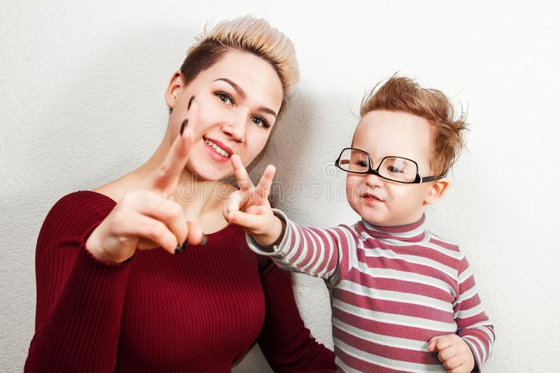Young mom and smiling baby boy with glasses shows v sign isolated on white background stock image