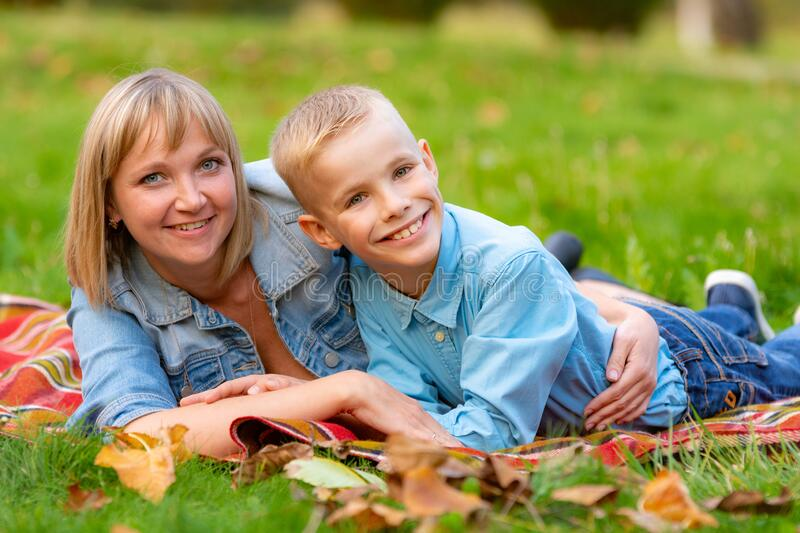 Young mom and teen son lie on bedspread on grass in city park royalty free stock photography