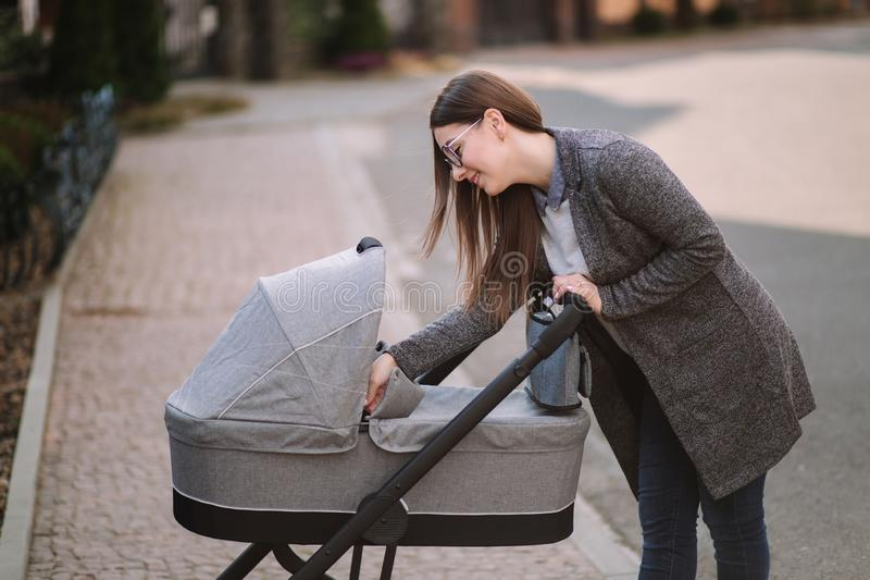 Young mom walking with daughter in stroller. Mother cares for the baby. Mom look in to the stroller and help baby to royalty free stock photos