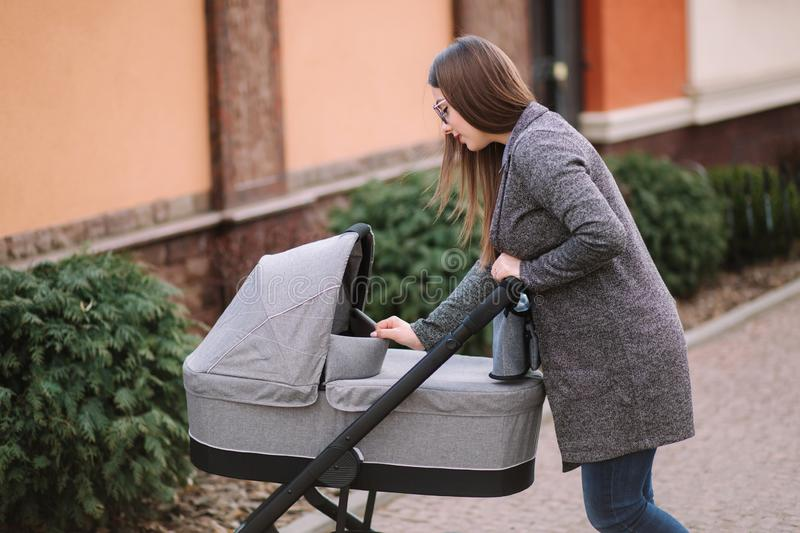 Young mom walking with daughter in stroller. Mother cares for the baby. Mom look in to the stroller and help baby to stock image