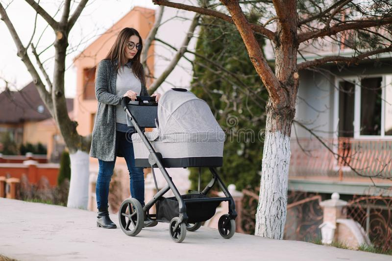 Young mom walking with stroller in the park. Stylish mother with baby royalty free stock photo