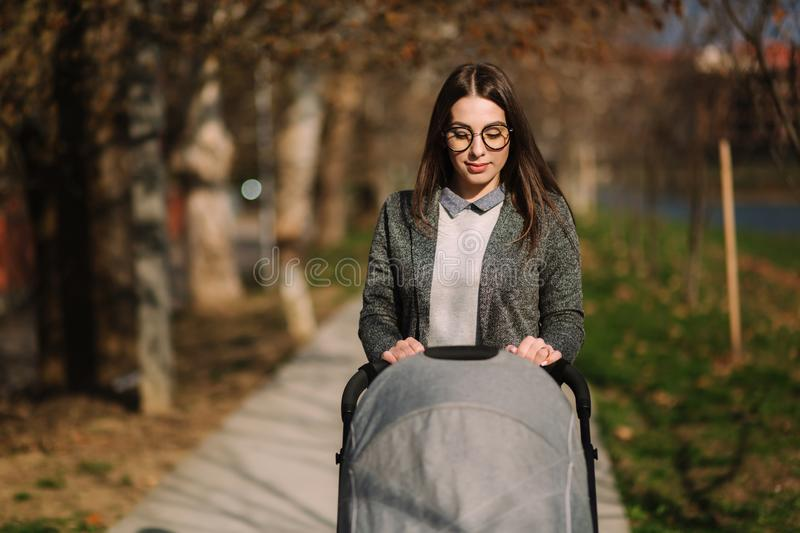 Young mom walking with stroller in the park. Stylish mother with baby royalty free stock photos