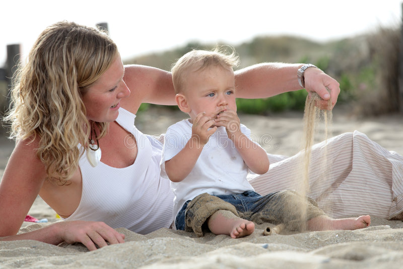Young mommy with her baby son. Young beautiful mommy playing with her baby son on the beach royalty free stock photos
