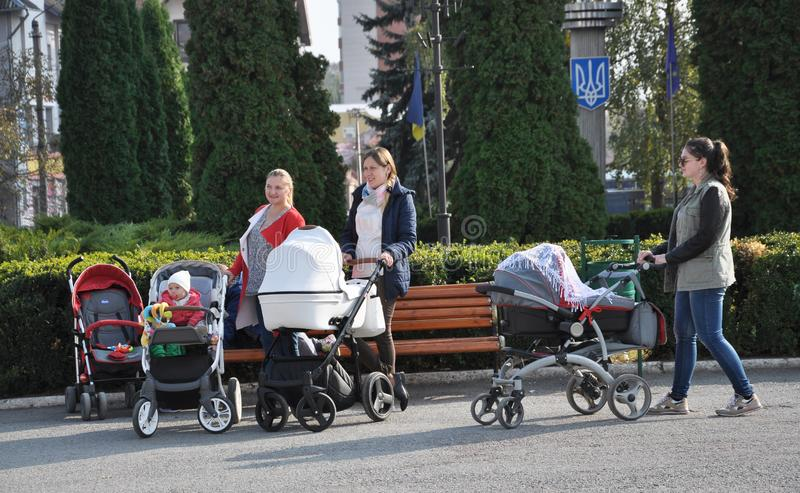 Young moms walking with children in strollers stock images