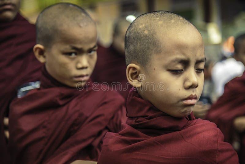 Young Monks in Mahandayon Monastery School, Mandalay, Myanmar. Young monks waiting in silence for lunch in Mahandayon Monastery School in Mandalay, Myanmar stock image