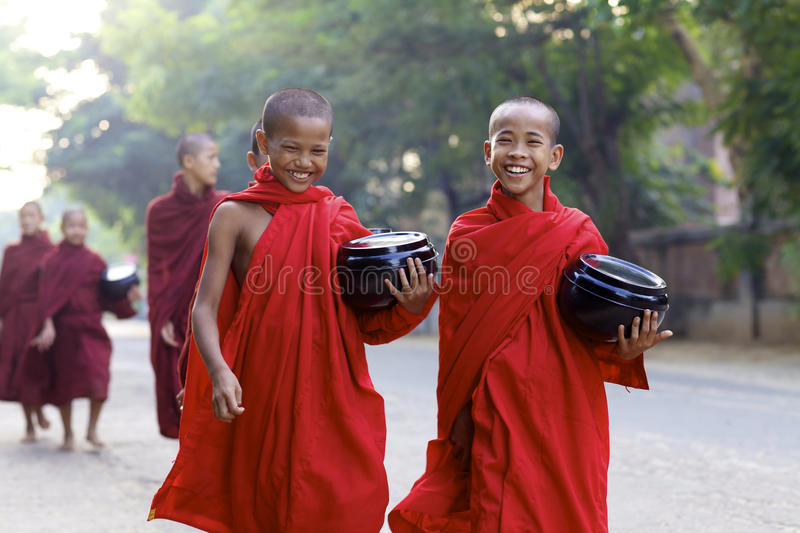 Young Monks Myanmar Burma. OLD BAGAN, MYANMAR- OCT 15: Unidentified young novice monks carrying bowls on morning alms walk in Old Bagan, Myanmar on October 15