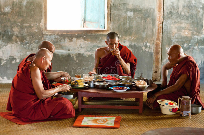 Young monks, Myanmar. Heho, Myanmar - March 01, 2011 - Group of monks in red robes eating lunch on the ground royalty free stock photos