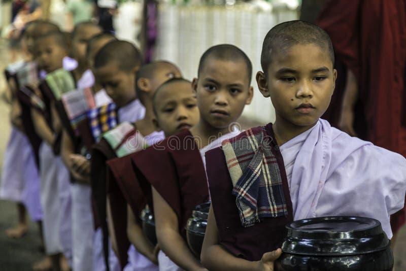 Young Monks in Mahandayon Monastery School, Mandalay, Myanmar. Young monks waiting in silence for lunch in Mahandayon Monastery School in Mandalay, Myanmar stock photos