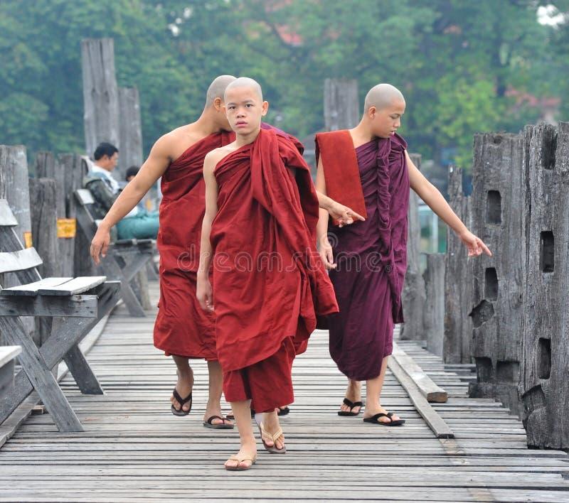 Young monks walking on the wooden bridge in Shan, Myanmar.  stock photos