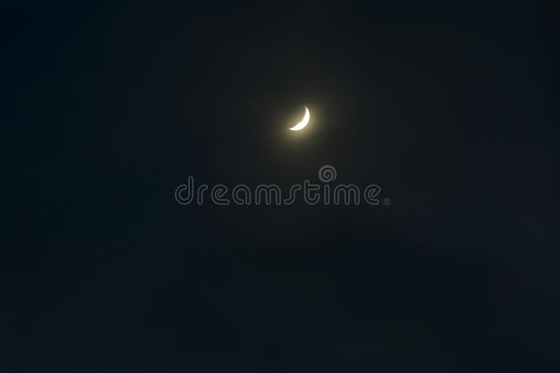 Young moon at the night sky. In the winter time royalty free stock photo