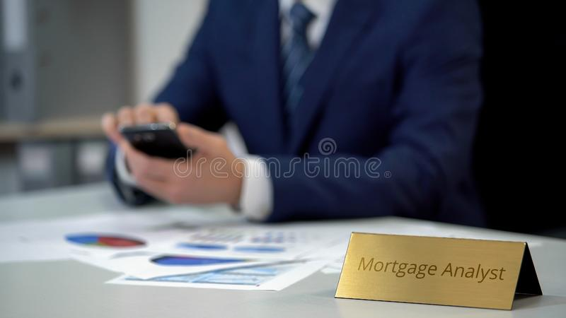 Young mortgage analyst using mobile phone, working on marketing report data. Stock photo royalty free stock photos