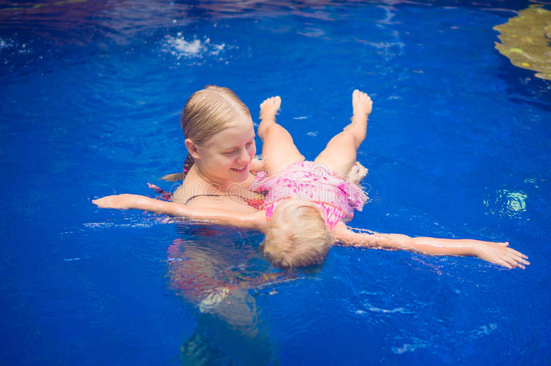 Young mother and adorable daughter having fun in pool. Learning royalty free stock image