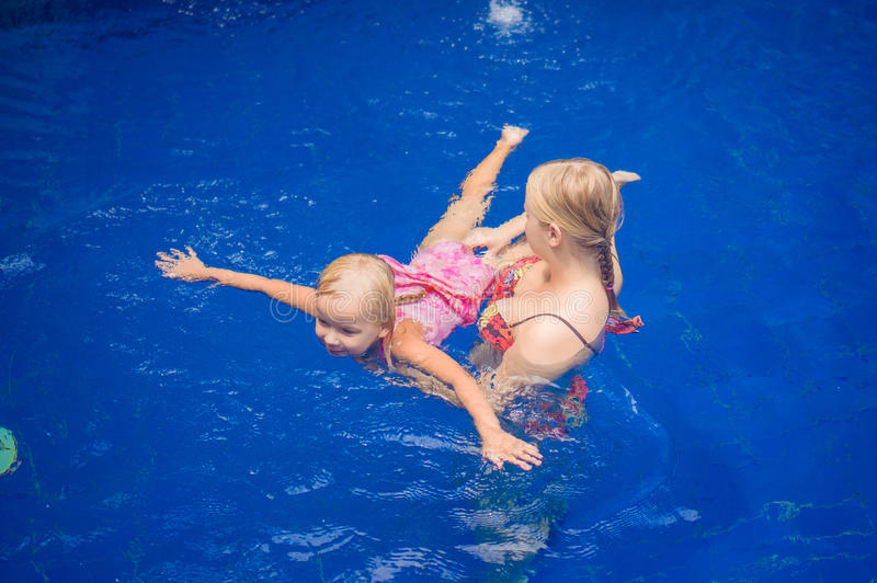 Young mother and adorable daughter having fun in pool. Learning stock images