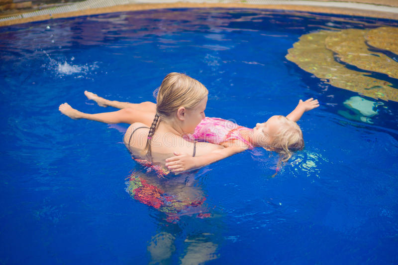 Young mother and adorable daughter having fun in pool. Learning stock photography