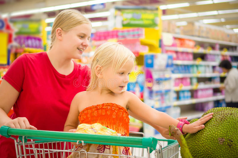 Young mother and adorable girl in shopping cart looks at giant j stock image