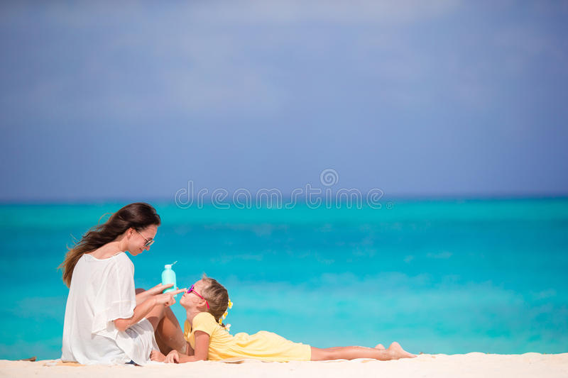 Young mother applying sun cream to daughter nose on bach vacation in hot day. Little daughter applying sun cream to her mother nose royalty free stock image