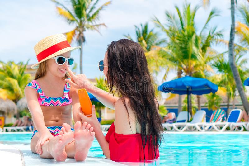 Young mother applying sun cream to kid nose in swimming pool. Young mother applying sun cream to daughter nose royalty free stock photography