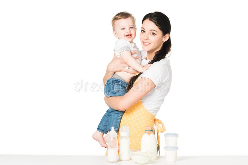 young mother in apron holding baby boy at table with children food stock photography