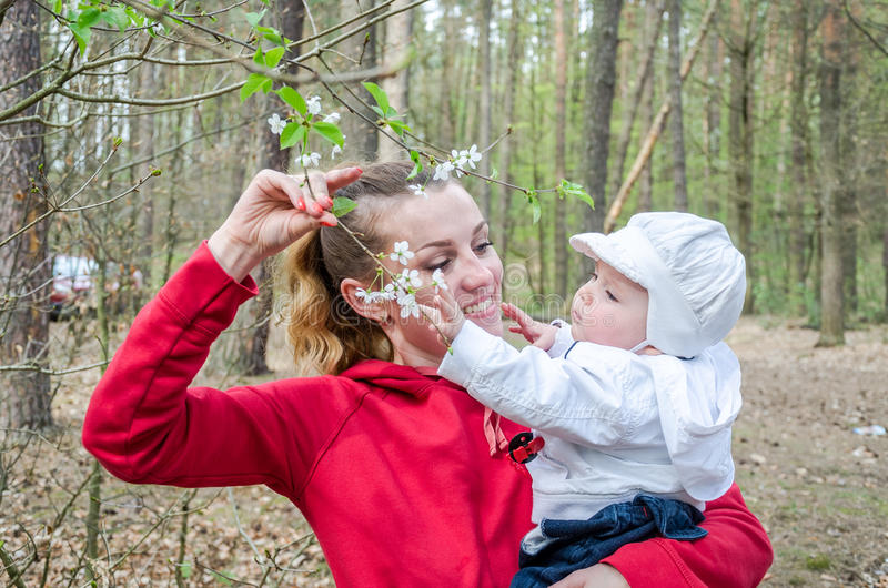 Young mother with baby daughter gives her daughter to smell the spring flowers on a tree stock photography