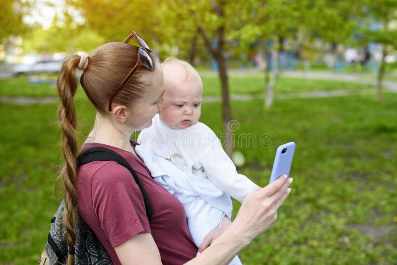 Young mother with a baby in her arms and uses a smartphone. Selfie with a child. Spring park.  stock photography