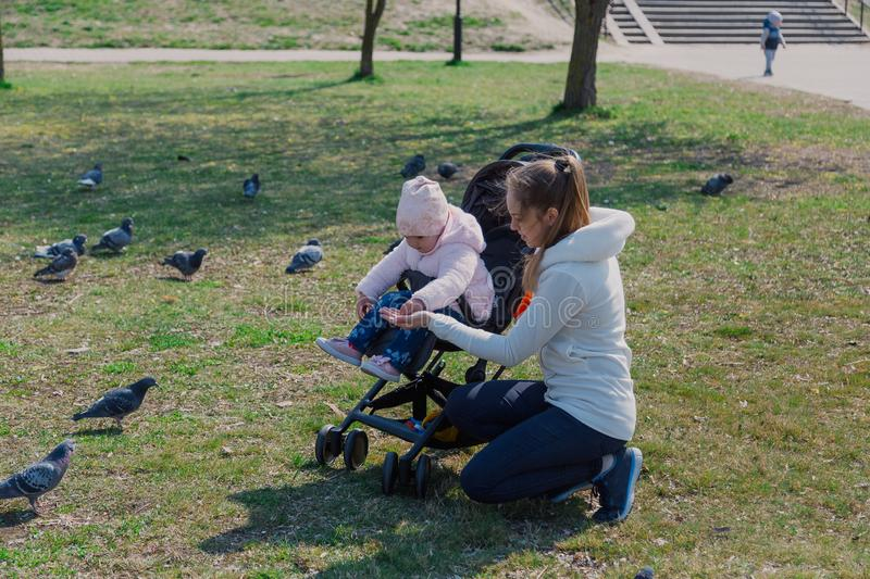 A young mother with a baby in a pram feeds pigeons. royalty free stock image