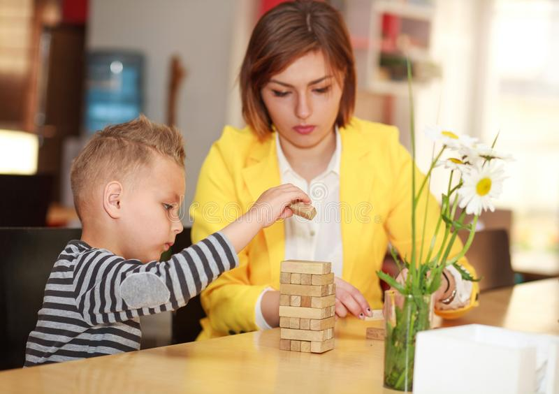 Young mother with baby son playing at home in room at table stock photography