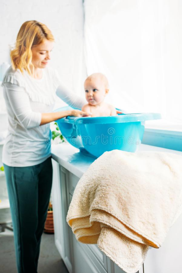 young mother bathing child in plastic bathtub royalty free stock photos
