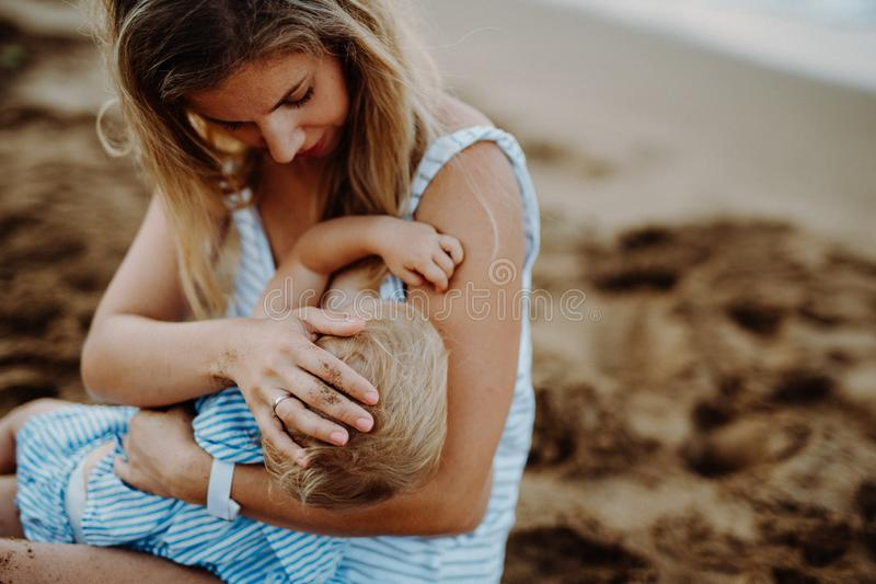 Young mother breasfeeding toddler daughter on beach on summer holiday. stock image